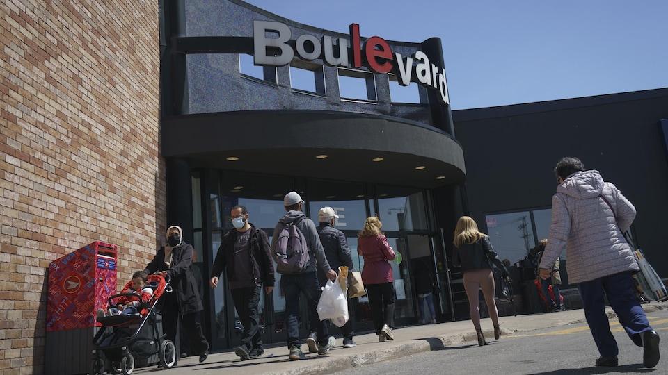 Des gens devant l'entrée principale du centre commercial Le Boulevard.