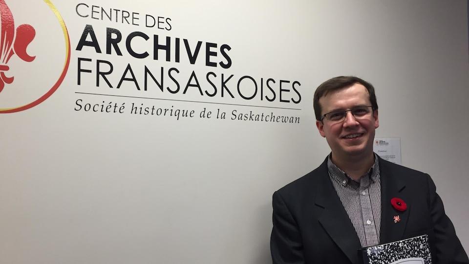 Dans un bureau, un homme prend la pose devant un mur où figure le logo du Centre des des archives fransaskoises. Il tient une chemise cartonnée d'archiviste dans ses mains.