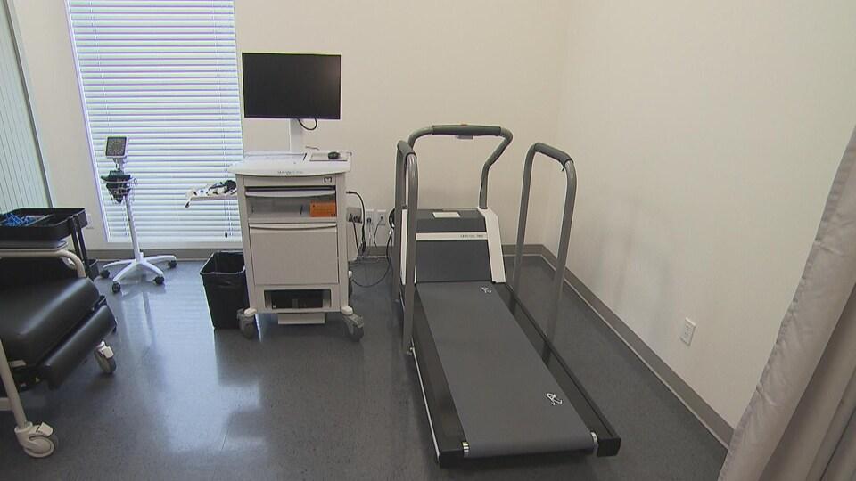 Un tapis de marche et un écran d'ordinateur dans une salle de consultation.