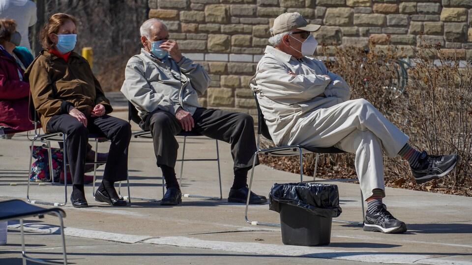 Des personnes âgées sont assises sur des chaises devant le centre de vaccination.
