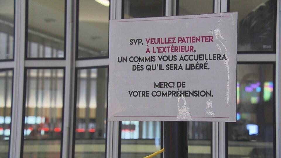 Une affiche demandant à attendre à l'extérieur d'un commerce.