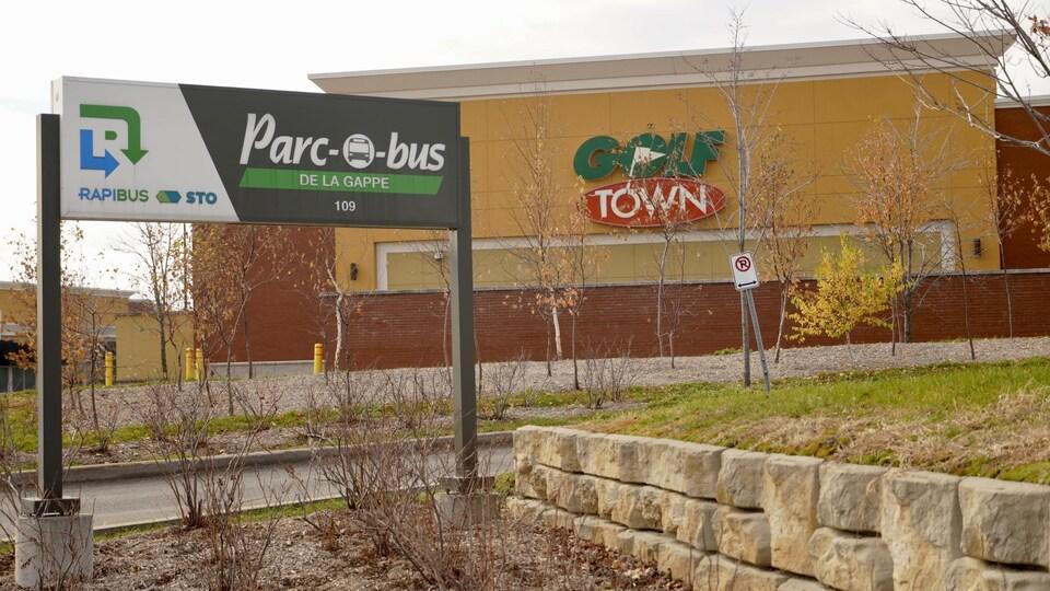 Un panneau ''parc-o-bus- du Rapibus de la STO devant un magasin Golf Town