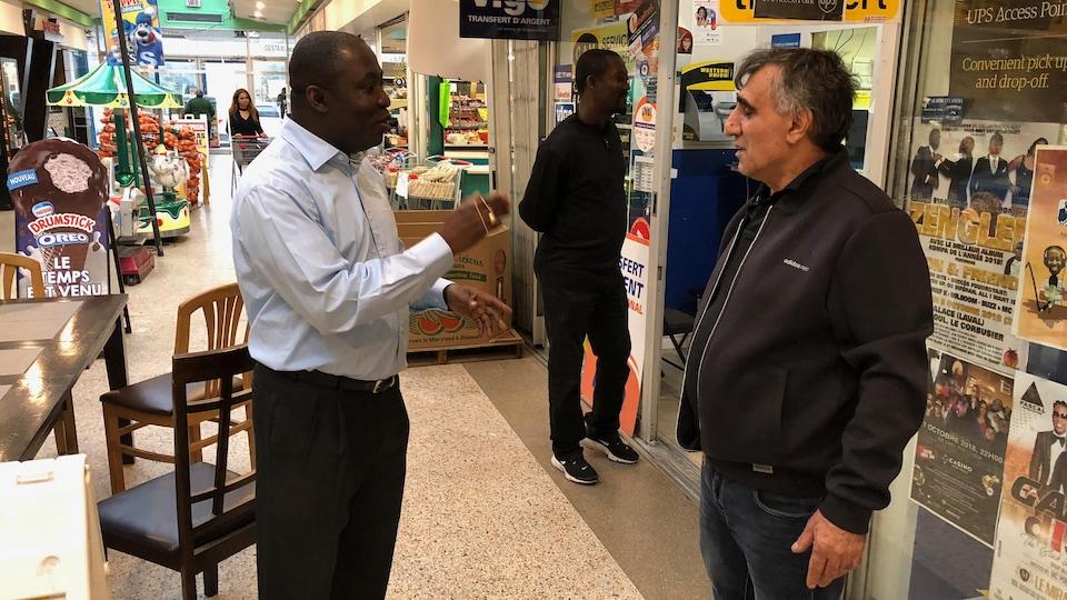 Okkas Altunatmaz d'origine turque et propriétaire de la Fruiterie Savannah discute avec le propriétaire de l'entreprise voisine, Monode Gracia, d'origine haïtienne qui possède Ges Taxi.