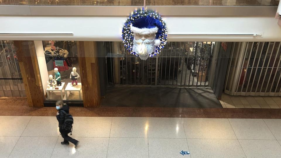 Une personne marche dans un centre commercial.