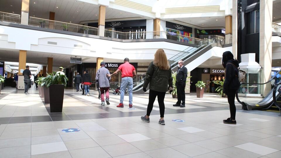 Quelques personnes circulent dans le centre commercial, surveillées par un agent de sécurité portant un masque de protection. Des autocollants par terre indiquent aux clients dans quelle direction circuler.