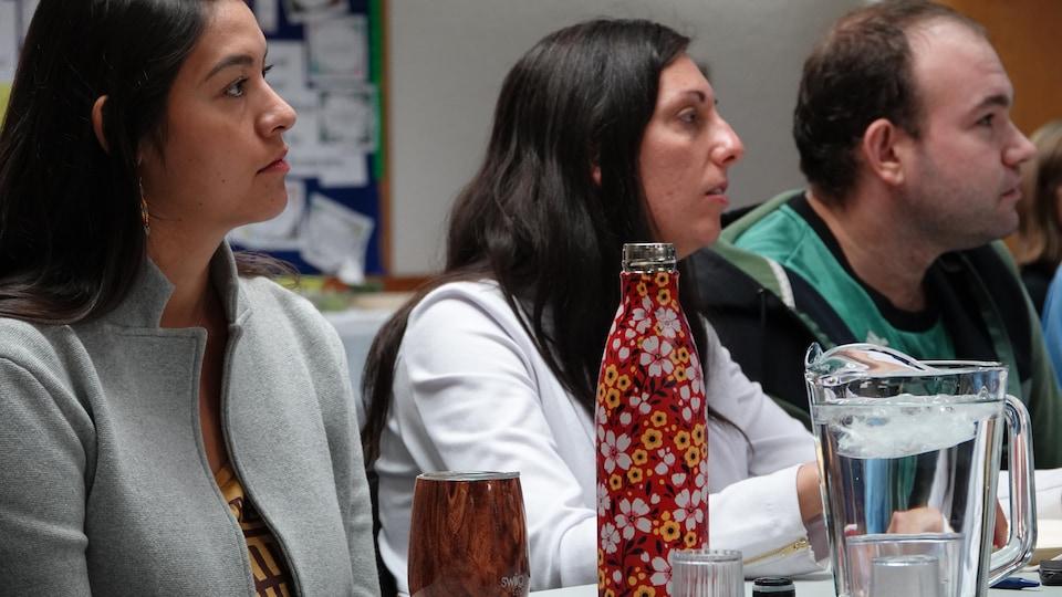 Trois personnes assises qui écoutent attentivement.