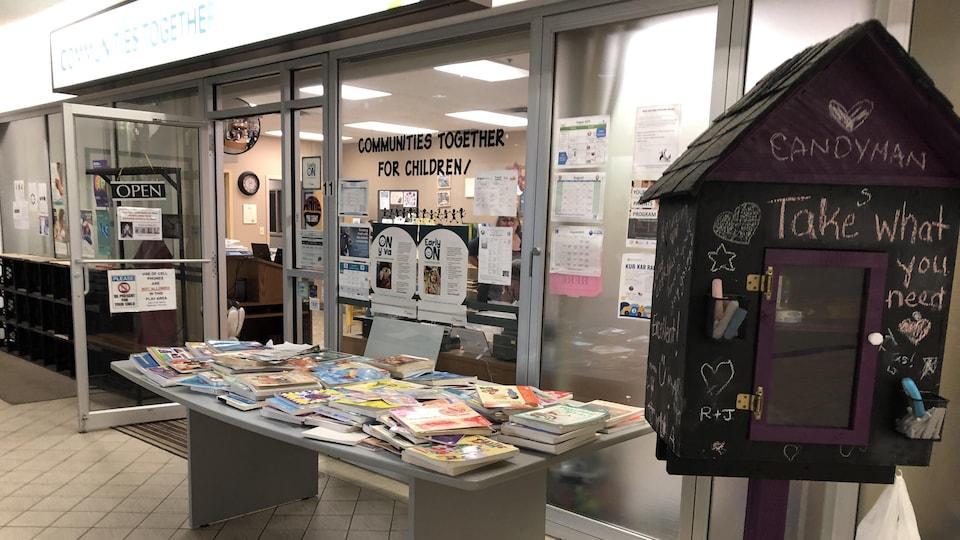Une table recouverte de livres et une boîte en bois devant l'entrée des locaux d'un organisme.