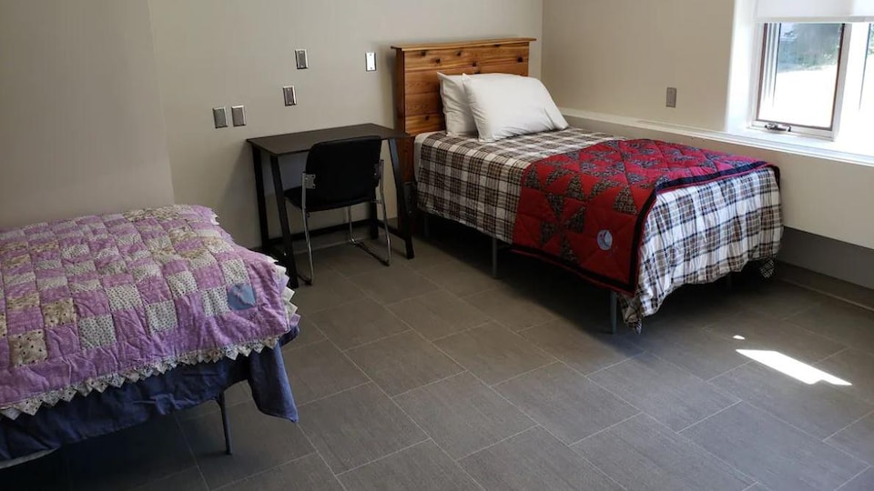 Deux lits simples dans une chambre avec un bureau et une chaise.