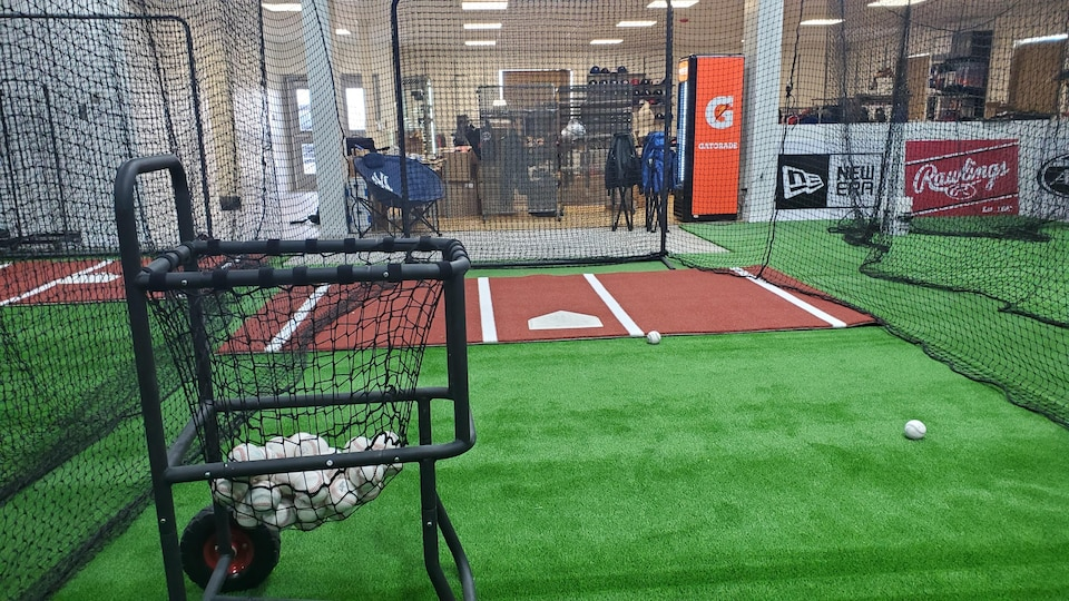 Un terrain de baseball synthétique entouré de filets. À l'arrière-plan, on distingue un magasin d'articles de sport.