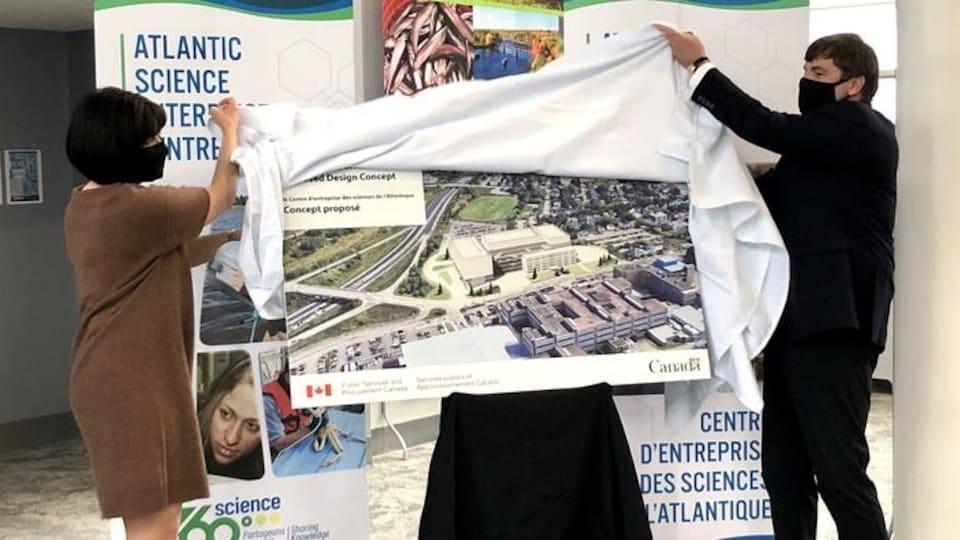 Ginette Petitpas-Taylor et Dominic LeBlanc retirent un toile blanche cachant une pancarte du concept.