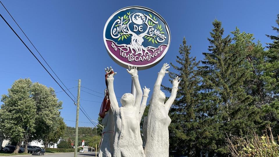 L'affiche du Centre de femmes au centre de statues de femmes.