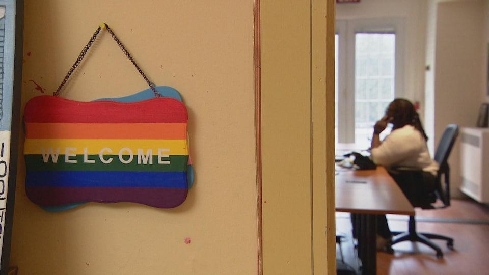 """Au premier plan, une affiche aux couleurs de l'arc-en-ciel, posée sur le mur, indique """"Welcome"""". À l'arrière-plan, une femme assise à une table parle au téléphone."""