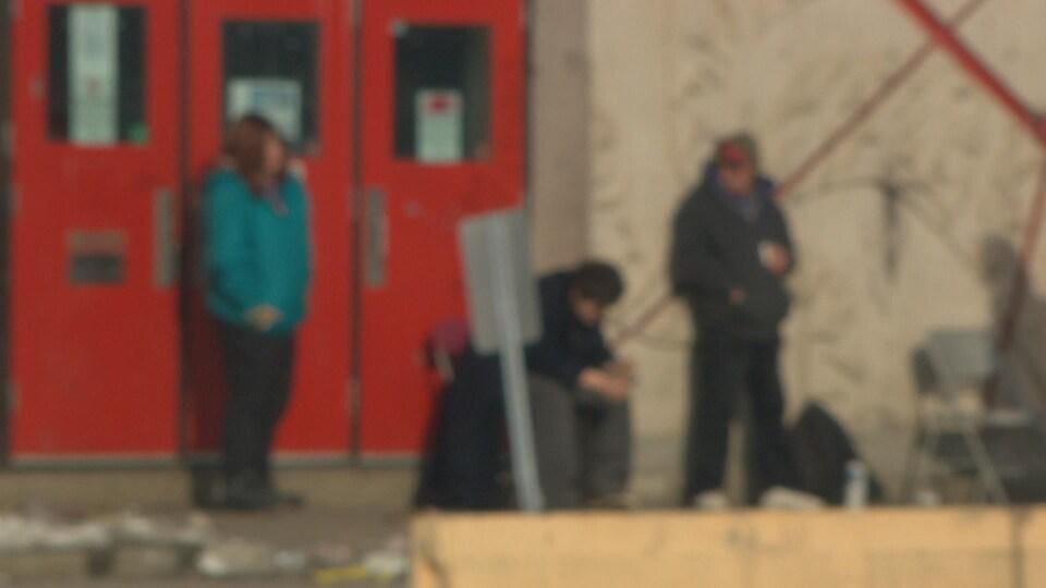 Trois sans-abri logés à Guertin devant les portes de l'aréna. La photo est volontairement hors focus.