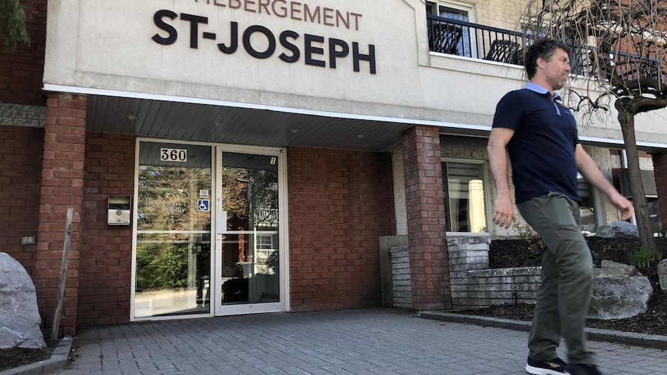 Un homme qui sort d'un centre d'hébergement pour aînés.