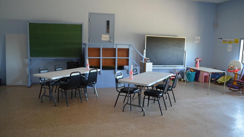 Une salle commune, où sont placées deux tables et des chaises