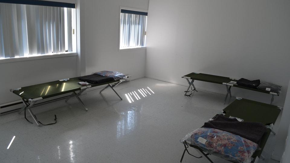 Une salle contient trois lits de camp.