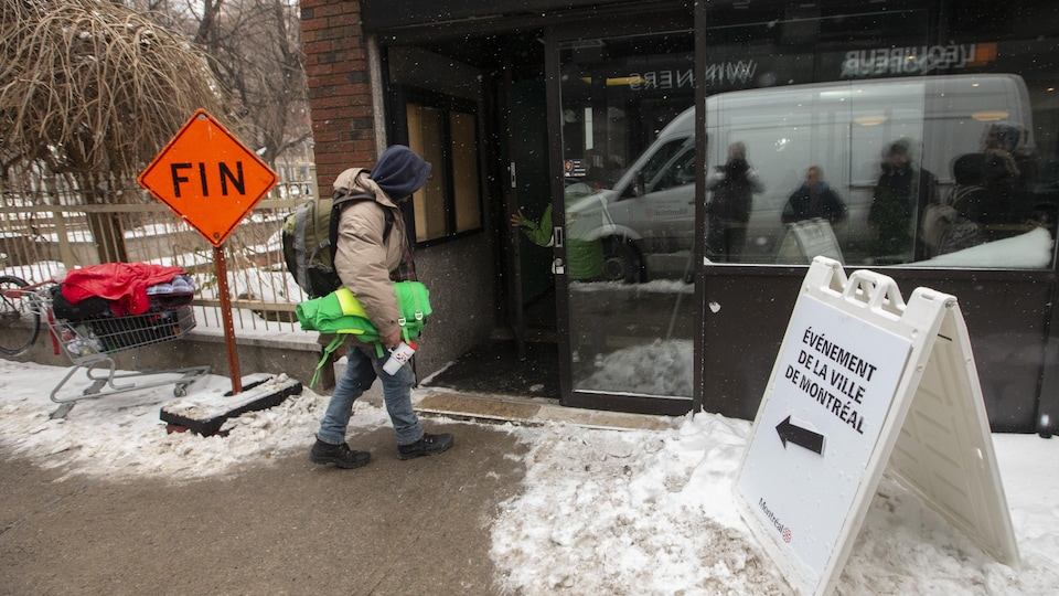 Un homme entre dans un centre d'aide pour itinérants.
