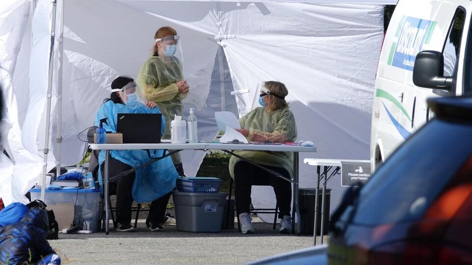 Trois travailleuses de la santé en équipement de protection autour d'une table aménagée devant un chapiteau dans un stationnement.
