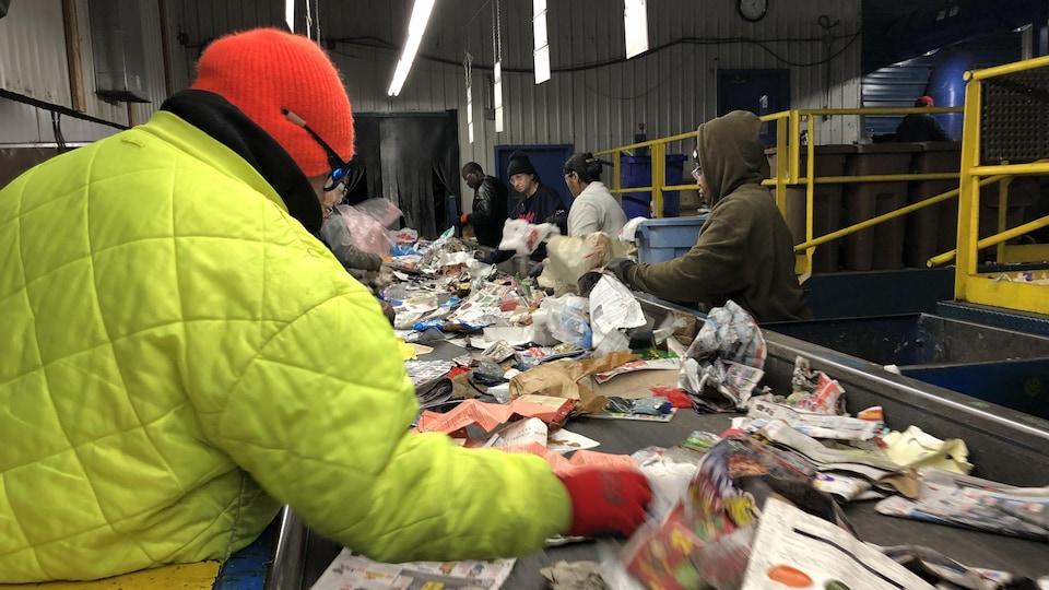 Des travailleurs trient les déchets qui défilent devant eux