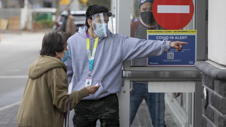 Un homme qui porte un masque et une visière indique à une femme âgée où elle doit aller pour se faire vacciner.
