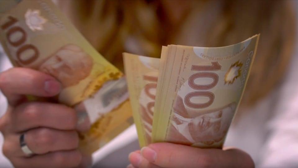 Femme anonyme qui compte des billets de 100 $.