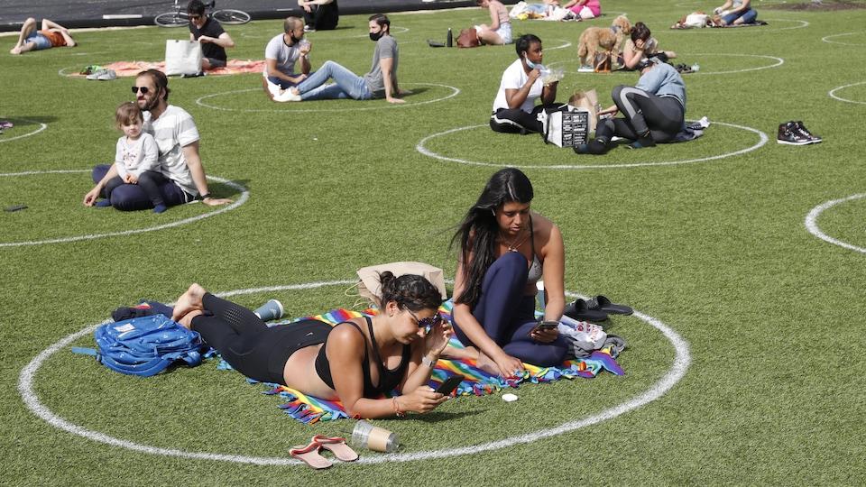 Deux femmes dans un cercle peint au sol dans un parc.