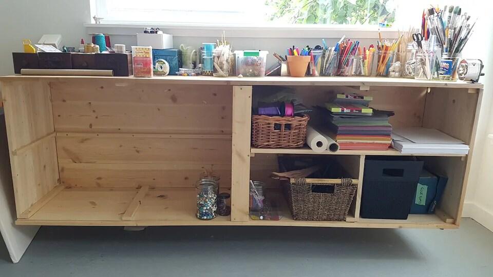 Un bureau en bois remplit de pots et de boites contenant du matériel d'art donc des crayons, des pinceaux, des ciseaux, de la colle, du fil et du papier.