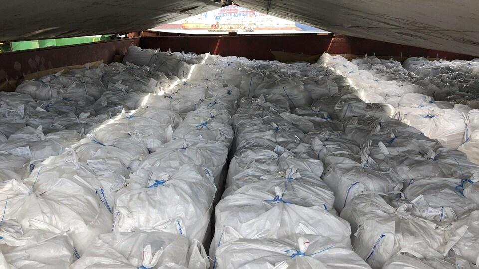 Une centaine de sacs fermés sont stockés dans un entrepôt.