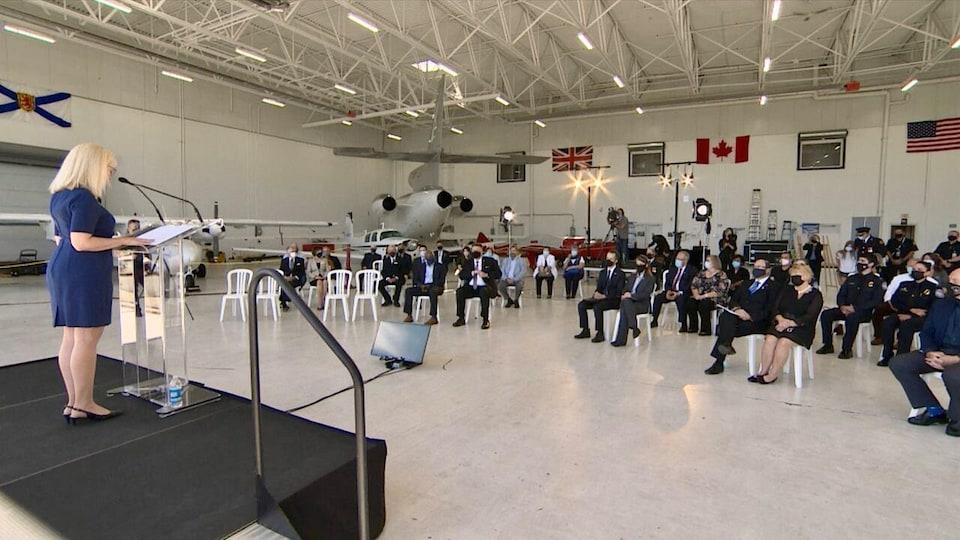Une femme debout sur une estrade devant des gens assis sur des chaises, dans un grand hangar.