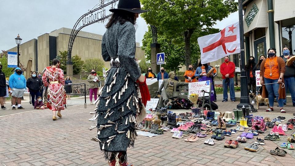 Une femme se recueille devant des chaussures d'enfants.
