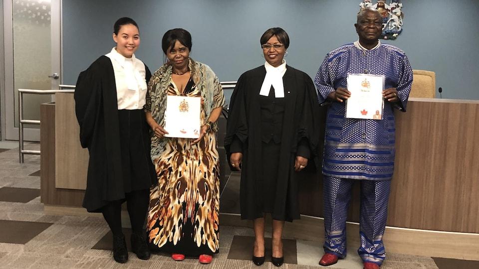 M. Edmond Kishila et Mme Marie Ndjibu posent avec la juge et la greffière lors de la cérémonie d'assermentation à la citoyenneté canadienne, le 15 août 2019, à la place du Canada, à Edmonton.