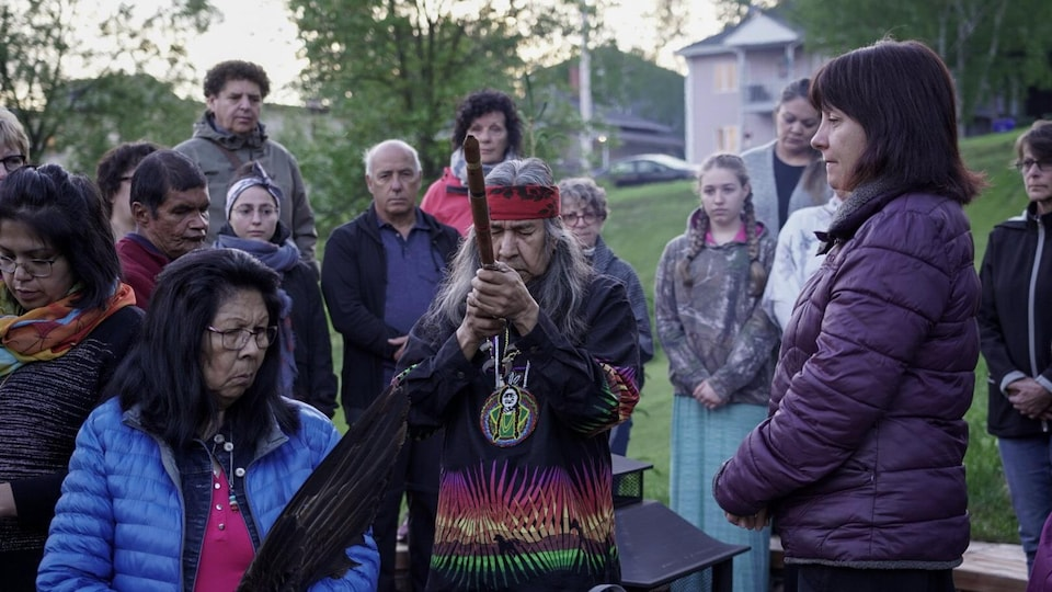 Un homme tient une pipe traditionnelle au sein de gens recueillis.