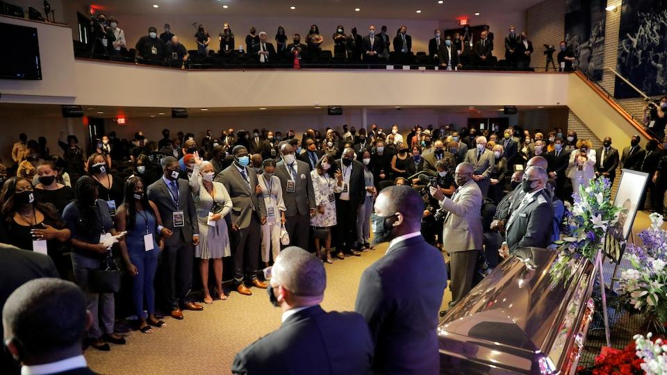 Des dizaines de personnes se tiennent debout, regardant en direction du cercueil, doré, de George Floyd.