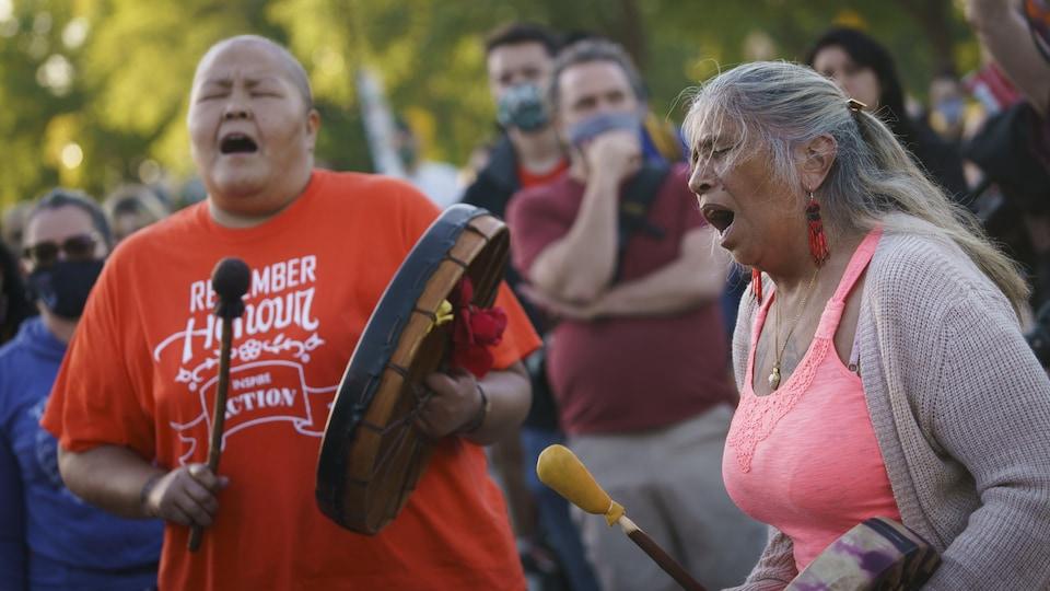 Deux femmes jouent du tambour en chantant.