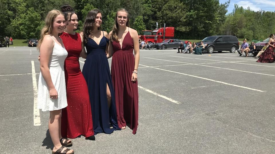 Quatre jeunes filles posent en robe de bal dans un stationnement.