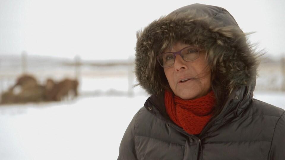 Sylvie Van Dersmissen, vêtue d'un manteau d'hiver à capuche et portant un foulard rouge.