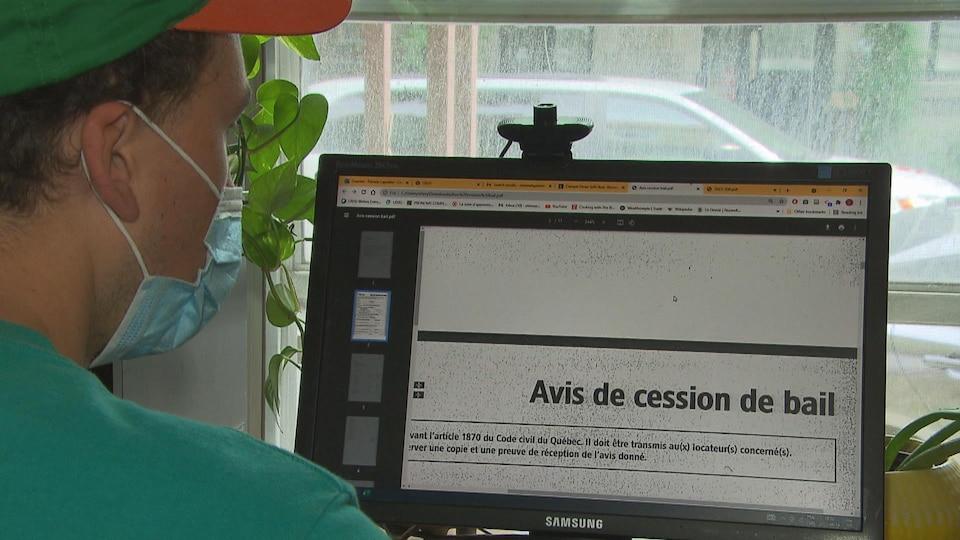 Un jeune homme assis, de dos, devant son ordinateur où un formulaire d'Avis de cession de bail est ouvert.