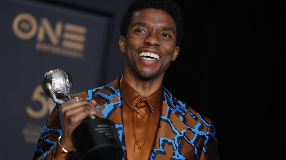 Boseman tenant un trophée et souriant.