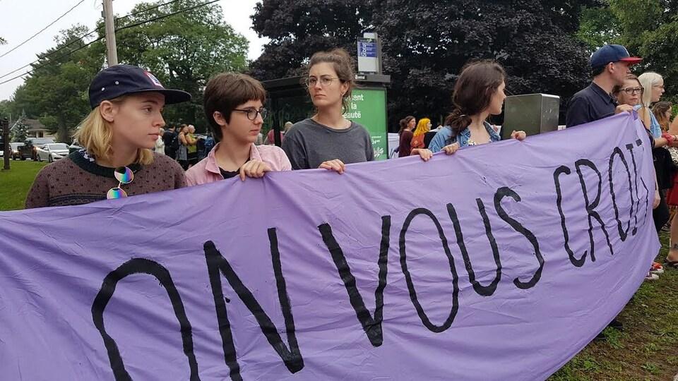 Des manifestants tiennent une banderole en appui aux victimes sur laquelle il est écrit : «On vous croit».