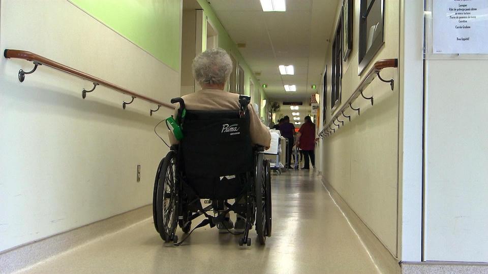 Une femme se déplace dans un couloir en fauteuil roulant.