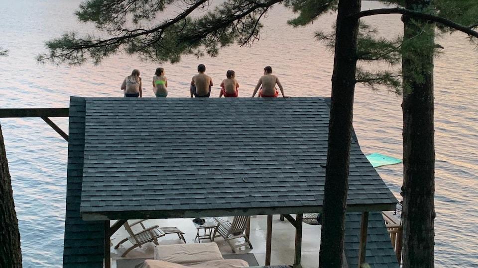Cinq enfants sont sur le toit du cabanon d'un chalet devant un lac.