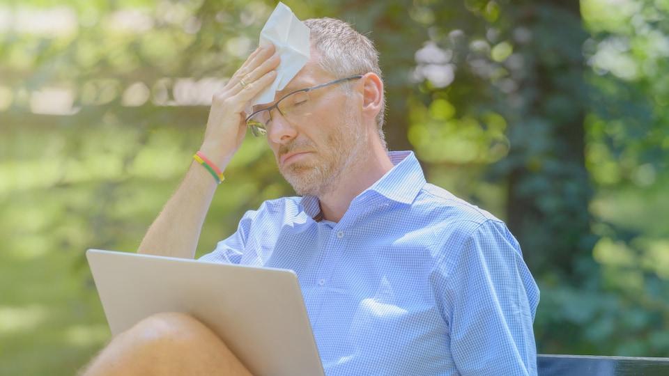 Un homme assis dans un parc, son ordinateur portable sur les genoux, s'éponge le front.