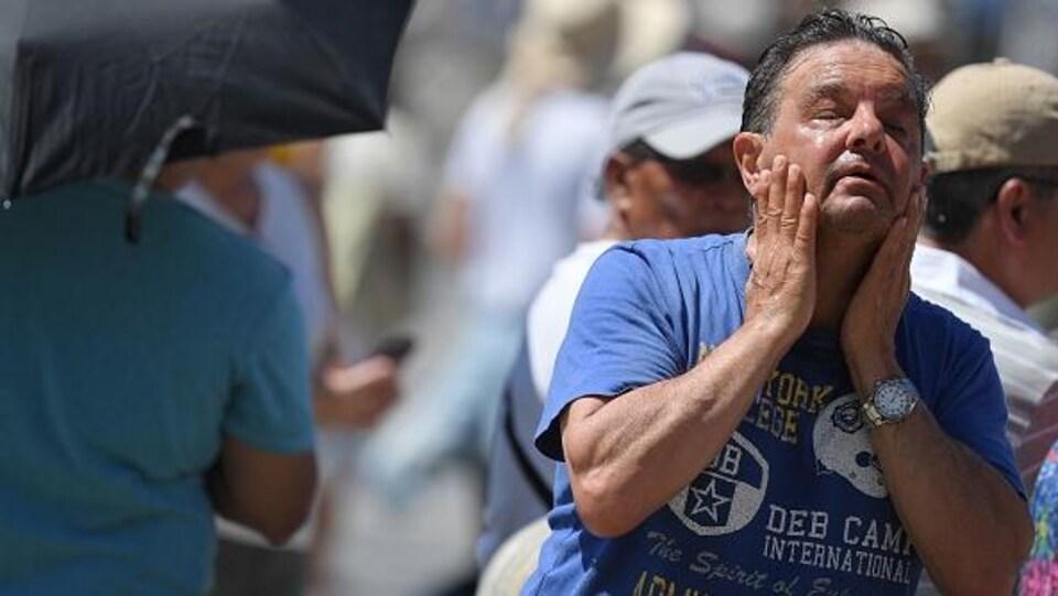 Un homme se rafraîchit à une fontaine publique le 30 juin 2019 sur la place Saint-Pierre au Vatican.
