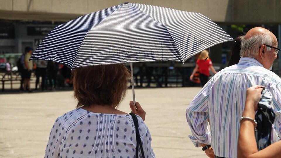 Des personnes utilisent des parapluies pour se mettre à l'ombre du soleil.