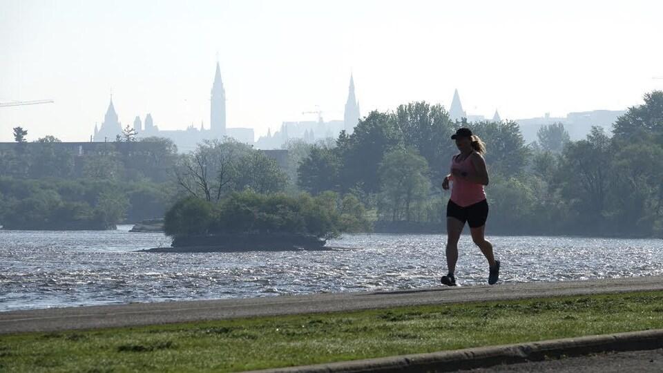 Une femme court le long de la rivière des Outaouais.