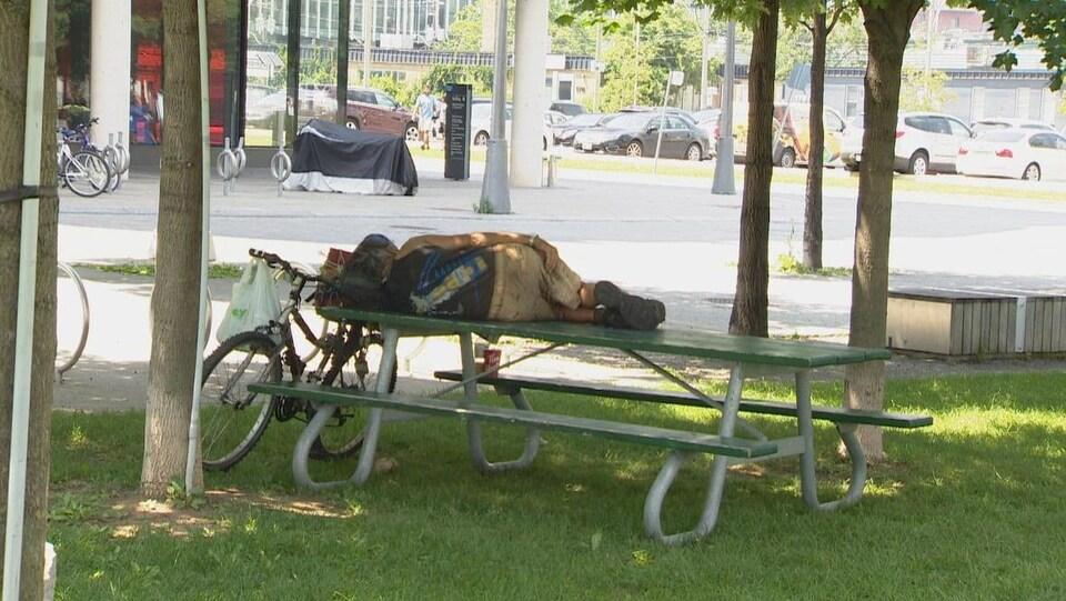 Une personne se repose sur une table de pique-nique lors d'une vague de chaleur.