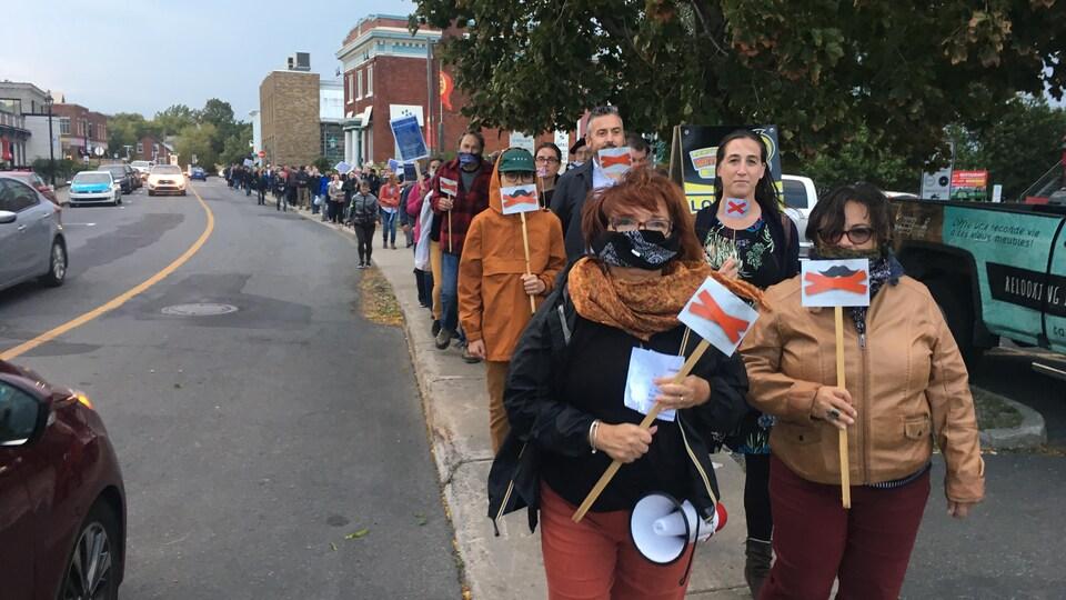 Une centaine de personnes, plusieurs arborant un bâillon, ont ainsi défilé dans le centre-ville de Chambly pour rappeler l'importance de la liberté d'expression. Le Mouvement réclame l'abandon, par la Ville, de toutes les poursuites et la fin de l'envoi de mises en demeure aux citoyens.