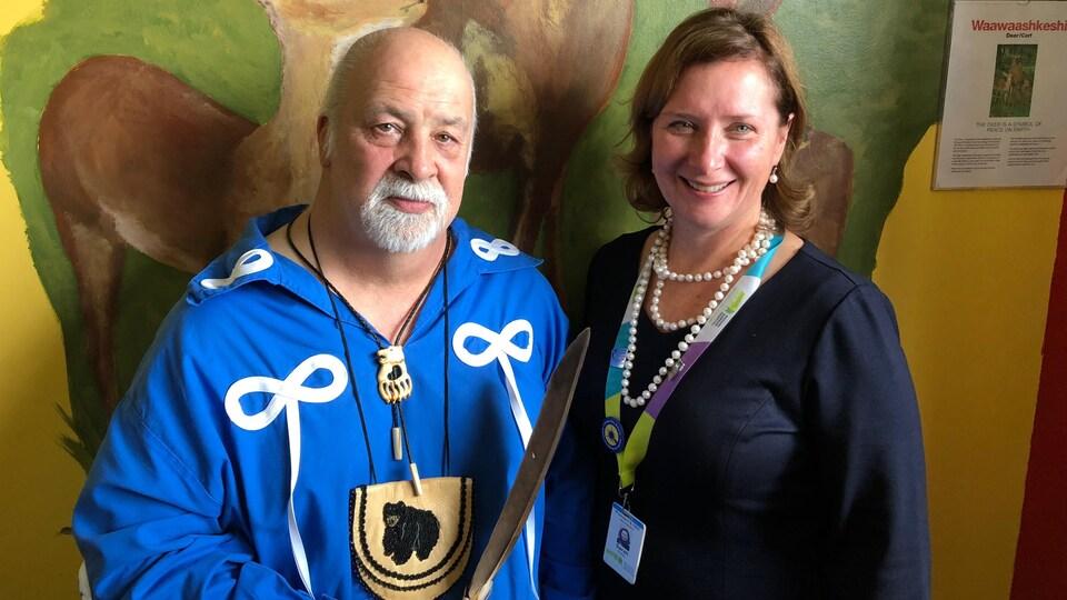 Petit Ourson brun et Sarah Downey, présidente de l'Hôpital Michael Garron devant un mur décoré de cerfs