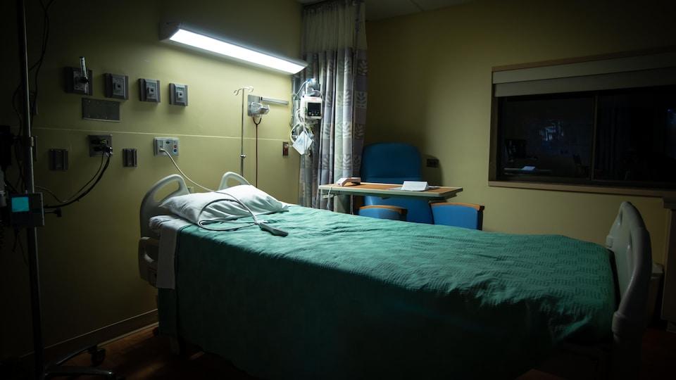 Un lit d'hôpital vide, la nuit.