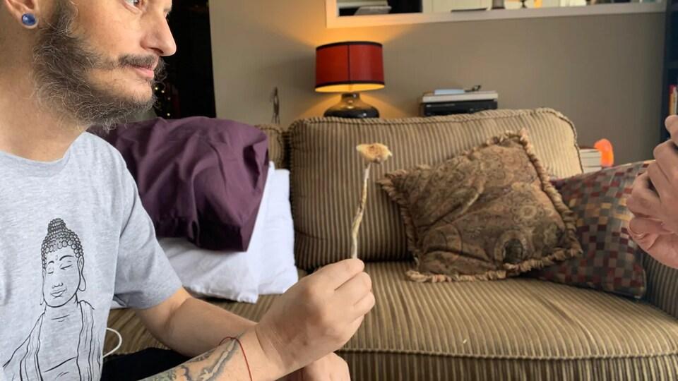 Tony White tenant un petit bout de champignon psychédélique à la main.